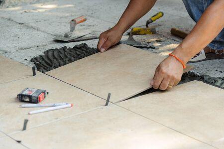 Tiler placing porcelain tile in position over adhesive. Floor tile installation Standard-Bild