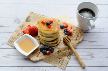 A cup of coffee and pancakes with ingredients on a white wooden background. Prepared ingredients for baking Standard-Bild