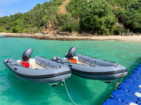 Inflatable boats tie with floating pier in front of a beautiful beach Standard-Bild