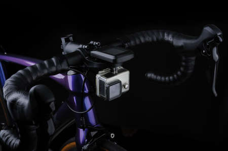 Bicycle handle bar with bike computer and front action camera on black background. Action camera on roadbike. Studio shot Imagens