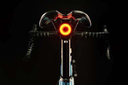 Close-up of illuminated bicycle tail light on black background