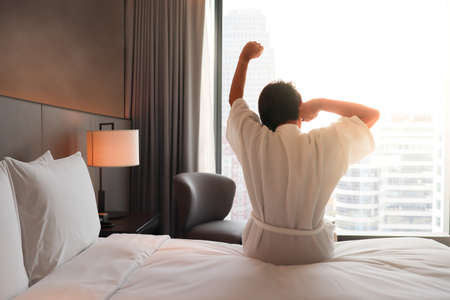 Rear view of a asian woman waking up in bed and stretching her arms. Woman stretching her arms up for get ready on active day