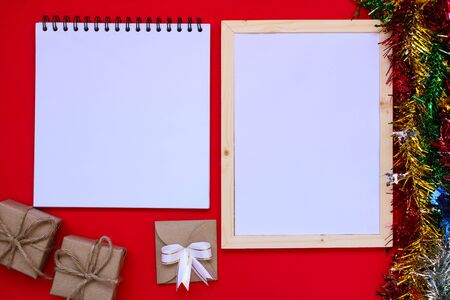 Note book and Christmas gift box on red background.