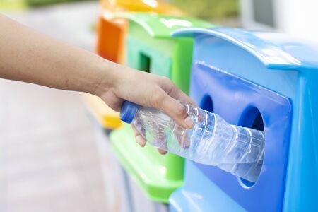 Le persone gettano bottiglie di plastica vuote nei cassonetti per il riciclaggio.
