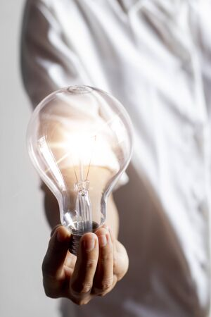 A young woman's hand with a light bulb Conceptual ideas with innovation and inspiration And creativity