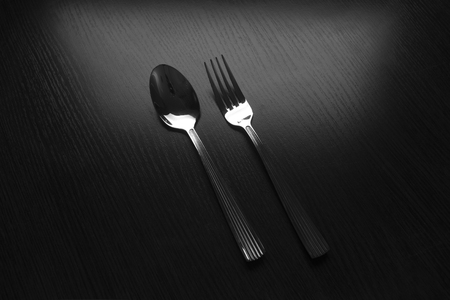 menus: fork and spoon on a black table dark tone