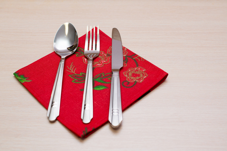 grunge silverware: Red napkin knife fork spoon on a wooden table