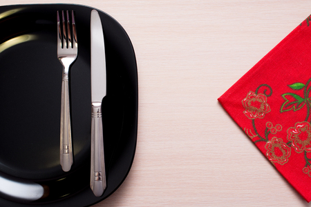 grunge silverware: Red napkin knife fork and a black plate on a wooden table