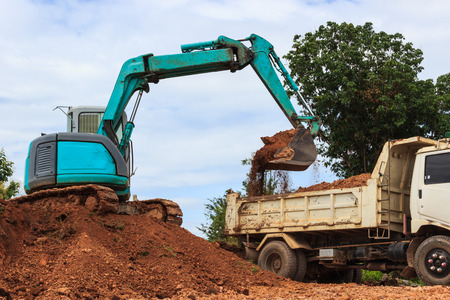 Industrial loader excavator moving earth and unloading on a dumper truck Stock Photo