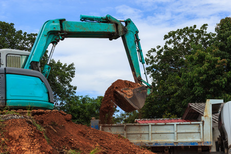 earth moving: Industrial loader excavator moving earth and unloading on a dumper truck Stock Photo