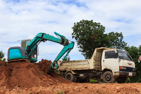 earth moving equipment: Industrial loader excavator moving earth and unloading on a dumper truck Stock Photo