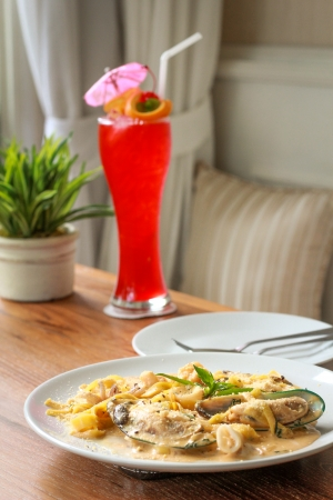 Fresh pasta with king prawns, mussels and a chilli and herb sauce. and Fruity cocktail with lemon lime and  with orange,cherries photo