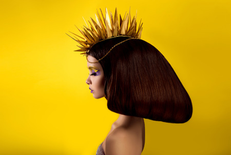 The avantaged portrait girl with an unusual make up, Portrait on a yellow background, custom volume hairstyle metal ornament in the form of fragments, fashionable toning
