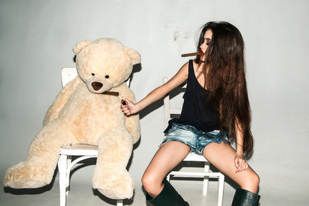 funny girl fooling around, giving bear smoking a cigar, goes mad