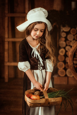 cinderella shoes: little girl in the image of Cinderella is holding a basket of fruits and vegetables , fashionable toning , happy childhood Stock Photo