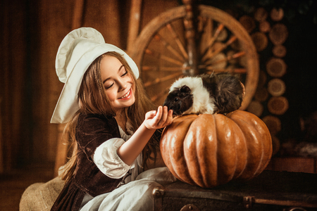 hands on hip: little girl in the image of Cinderella feeds the mouse out of the hands , hip toning , happy childhood Stock Photo