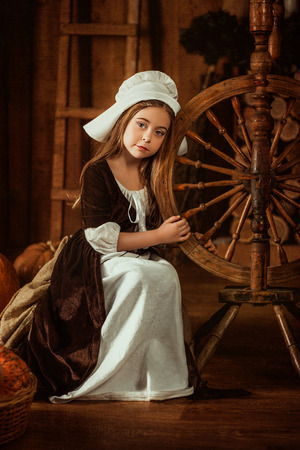 cinderella shoes: little girl in the image of Cinderella sits near a spinning wheel from the hands , hip toning , happy childhood