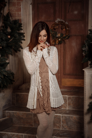 Beautiful little girl in a cozy cardigan stands on the background Christmas decorations , fashionable toning , creative color Stock Photo