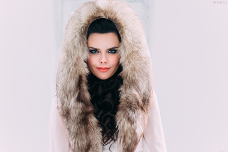 fur hood: Luxurious brunette in a fur coat with fur hood stands on a snow-covered meadow , fashionable toning , Creative Colors Stock Photo