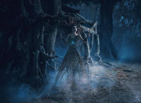 De geest dwaalt de bossen in het duistere magie bos meisje boom wortel schoot in de buurt van de machtige eik, mystiek beeld, spreuken, mode creatieve kleur toning Stockfoto