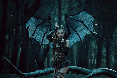 bate: niña vampiro, un demonio con alas de murciélago, un súcubo, a través del bosque oscuro chica caminando con un bate de enormes alas y equipo atractivo, tonificación de moda, colores creativos informáticos Foto de archivo