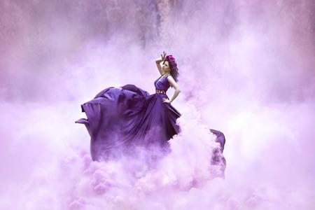 Lady in einem Luxus-üppigen lila Kleid wirbelt im Rauch, fantastische Schuss, Märchenprinzessin wird im Herbst Wald, moderne Tonen, kreativ Computer Farben zu Fuß Standard-Bild