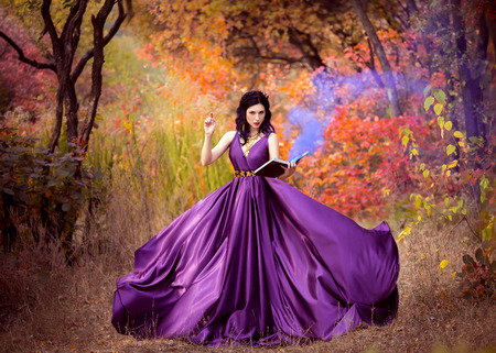 Lady in a luxury lush purple dress swirls in the smoke,fantastic shot,fairytale princess in walking in the autumn forest,fashionable toning,creative computer colors