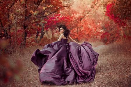 Señora en un vestido púrpura exuberante, fantástico disparo de lujo, princesa de cuento está caminando en el bosque de otoño, tonificación de moda, colores creativos informáticos