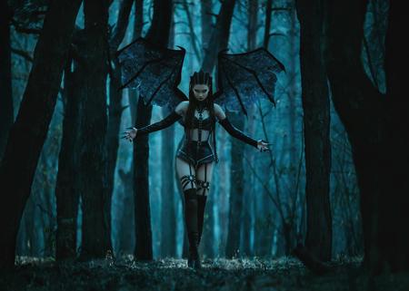bruja sexy: niña vampiro, un demonio con alas de murciélago, un súcubo, a través del bosque oscuro chica caminando con un bate de enormes alas y equipo atractivo, tonificación de moda, colores creativos informáticos Foto de archivo