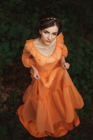 The beautiful countess in a long orange dress  is walking in a green forest full of branches, elf,  Princess in vintage dress, the queen of the forest,fashionable toning creative computer colors
