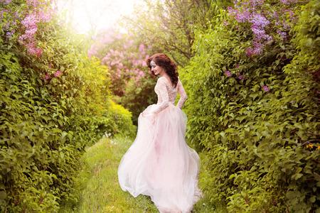 La jeune fille en robe pastel transparent avec un train, avec un diadème dans les cheveux. Fée se dresse au sommet des collines verdoyantes, Creative mode tonification couleur Banque d'images - 52505351