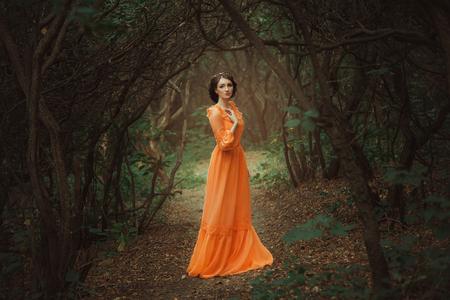 La hermosa condesa en un vestido largo de color naranja está caminando en un bosque verde lleno de ramas, duende, princesa en el vestido de época, la reina de la selva, tonificación colores de moda creativa de ordenador