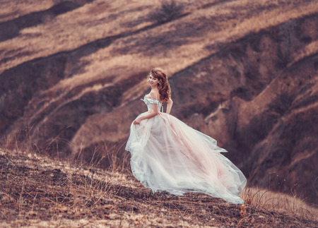The girl in transparent dress with long flying pastel train stands on the top of the mountain , Shabby chic, boho style , fashion creative computer color rendering Banque d'images
