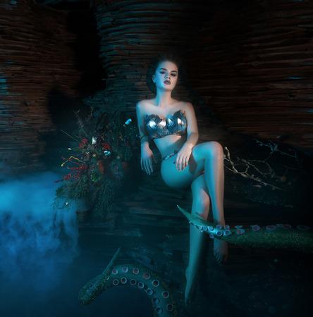 belle fille mince dans les bras d'un poulpe, tentacules enrouler autour du corps, tir fantastique, tonifiant, les couleurs à la mode créatives Banque d'images