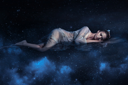 Beautiful young girl sleeps in the arms of space among the stars , fantaskicheskaya fotoshoot , fashionable toning , creative color