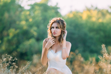 fun in the sun: beautiful blonde girl in a light white dress walking in the green fields and spikelets , fashionable toning , creative color