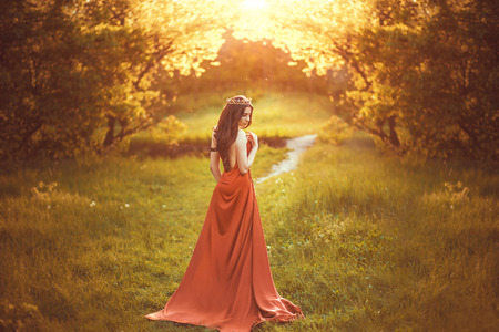 cinderella dress: Beautiful young princess in a long red dress walks among the green plants in the woods, a fashionable toning, creative color Stock Photo