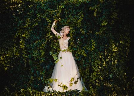 La belle comtesse dans une longue robe pastel se promène dans une forêt verte pleine de branches, elfe, princesse en robe vintage, la reine de la forêt, tonification mode couleurs informatiques créatif Banque d'images - 55306197