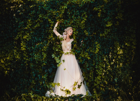 The beautiful countess in a long pastel  dress  is walking in a green forest full of branches, elf,  Princess in vintage dress, the queen of the forest,fashionable toning creative computer colors 版權商用圖片