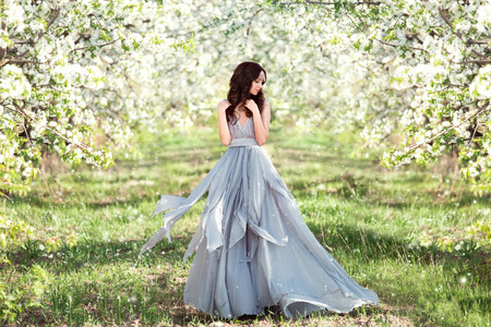 beautiful spring walk in the garden among the blooming trees in Aprila lady in a long dress pastel , creative computer colors, fashionable toning Banque d'images