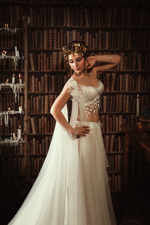 muse: girl muse of the poet in Greek robes standing in the room full of books and inspiring fashion creative color toning