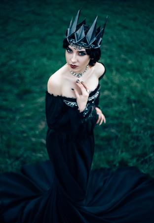 sneaks: dark evil queen sneaks through the green field at cosplay moviesnow white, wild Princess , vampire , hip toning , creative color,dark boho