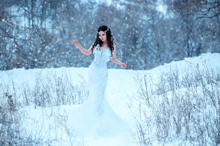 Luxurious brunette in a white dress standing in a snowy forest , Snow Queen, fairytale princess ,a fantastic shot,a fashionable toning , creative color