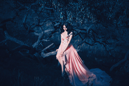 Lady in a luxury lush pink pastel dress   near the tree,fantastic shot,fairytale princess is walking in the autumn forest,fashionable toning,creative computer colors