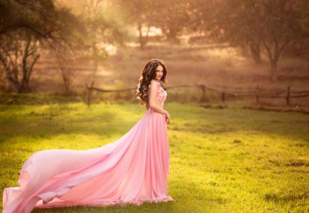 La ragazza in abito rosa trasparente con un lungo strascico di volo, principessa delle fiabe si erge sulla cima delle verdi colline, il colore del computer creativo tonificante alla moda