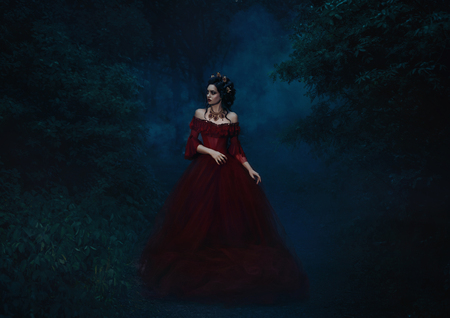 Beautiful girl   standing in a red dress standing on the gothic background blowers forests, forest princess, halloween , dark boho , fashionable toning , creative color Banque d'images