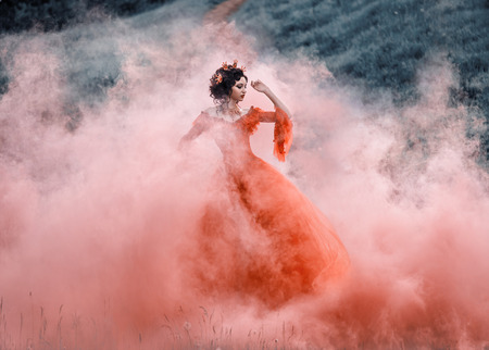 Lady in a luxury lush red dress swirls in the smoke,fantastic shot,fairytale princess is walking in the autumn forest,fashionable toning,creative computer colors