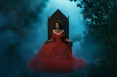 donkere boze koningin zittend op een luxuus troon, donker boho, wilde Prinses in rode jurk, vampier, heup toning, creatieve kleur, donker boho Stockfoto
