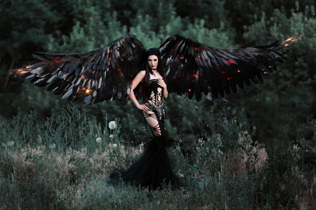black wings: Black Angel. Pretty girl-demon with black wings. An image for Halloween. Image of an old book of fairy tales. Fashionable toning