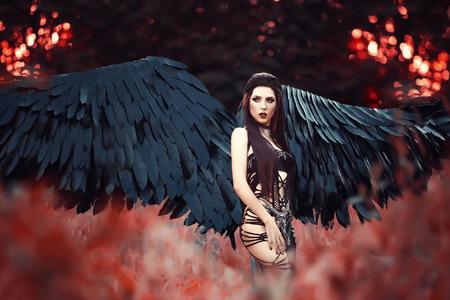 Zwarte engel. Mooi meisje-demon met zwarte vleugels. Een beeld voor Halloween. Afbeelding van een oud boek van sprookjes. modieuze toning